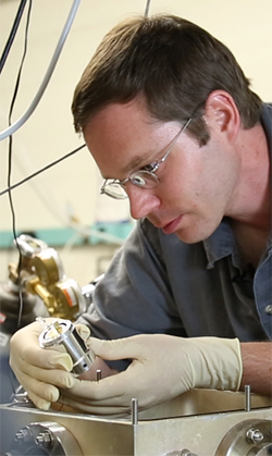 Research Assistant Professor Alexander Albrecht examines the world's first solid-state cryocooler – a device developed and built at The University of New Mexico.